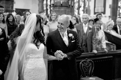 dad giving his daughter away at a wedding ceremony at st Peters church in Prestbury
