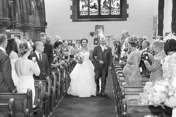Photo of the father of the bride walking the bride down the aisle