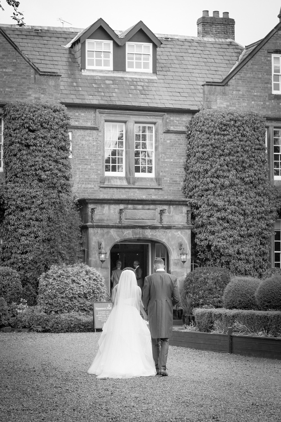 Photo of the bride and groom walking back into Nunsmere Hall in Cheshire