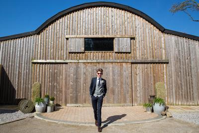 Groom walking at a rustic barn